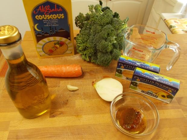 1 carota1/2 cipolla1 spicchio d'aglio1 broccolo (oppure 1 zucchina)1 falda di pomodoro secco con i cucchiaio del suo olio2 cucchiai di olio EVO2 scatole di sgombri sott'olio250 g di cous-cous precotto250 g di acqua